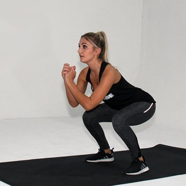 Fitness model performing a jumping squat