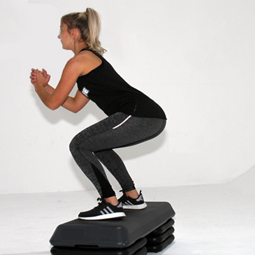 Fitness model performing a box jump exercise