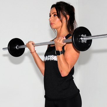 Fitness model performing a barbell curl