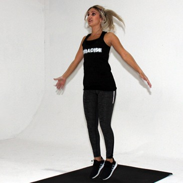 Fitness model performing a jumping jack