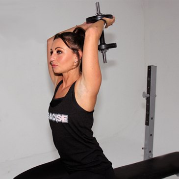Fitness model performing a tricep extension exercise