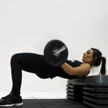Fitness model performing a barbell thrust
