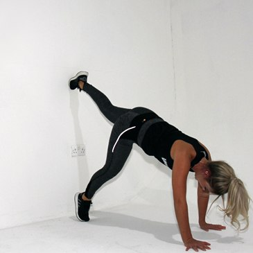 Fitness model performing a handstand wall hold exercise